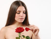 Cute beautiful woman tears off petals of red rose on white backg Stock Photos