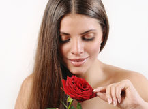 Cute beautiful woman tears off petals of red rose Royalty Free Stock Image