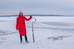 Cute beautiful young woman with ice drill stands on frozen river and prepares for fishing royalty free stock images