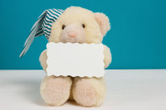 Cute beige bear with a nightcap and card on white, blue background.Selective focus, film effect, space for text. Cute beige bear with a nightcap and card on Stock Photo
