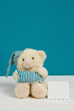Cute beige bear with a nightcap, pillow and card on white, blue background. Selective focus, film effect, copy-space. Cute beige bear with a nightcap, pillow and Stock Images