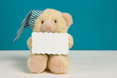 Cute beige bear with a nightcap, pillow and card on white, blue background. Selective focus, film effect, space for text.  Royalty Free Stock Photos