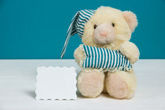 Cute beige bear with a nightcap, pillow and card on white, blue background. Selective focus, film effect, space for text.  Royalty Free Stock Image