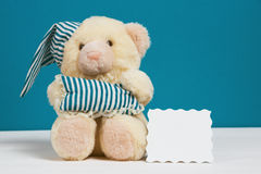 Cute beige bear with a nightcap, pillow and card on white, blue background. Selective focus, film effect, space for text. Cute beige bear with a nightcap, pillow Stock Photo