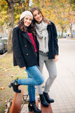 Cute best friend girls standing on a bench smiling Royalty Free Stock Images