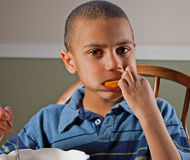 Cute Bi-Racial Boy Eating Orange Stock Photo