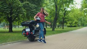 Cute biker girl with helmet posing by motorcycle stock footage