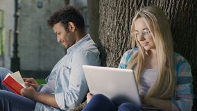 Cute biracial guy glancing at blonde girl with laptop with tenderness and love. Stock footage stock footage