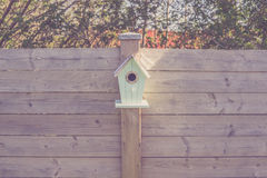 Cute birdhouse on a wooden fence Stock Images