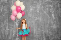 Cute birthday girl with colorful balloons. Near grunge wall Royalty Free Stock Photos