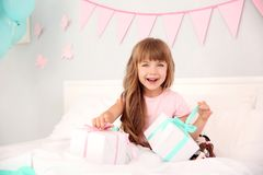 Cute birthday girl opening boxes with presents. While sitting on bed at home Royalty Free Stock Photography
