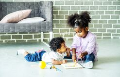 Cute black african american little girl and boy drawing book on floor indoors,  African people - Children