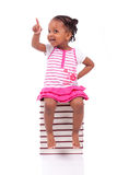 Cute black african american little girl seated in a stack of boo. Ks, isolated on white background - African people - Children Stock Images