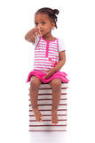 Cute black african american little girl seated in a stack of boo Royalty Free Stock Images