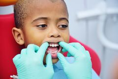 Cute black baby boy African American smiling sitting in the dental chair. At the examination at the children`s dentist stock photos