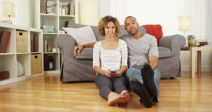 Cute black couple sitting on floor in living room Stock Images
