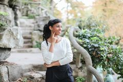 Cute black female person standing near rock and stone stairs in park, having ponytail. Cute black female person standing near rock and stone stairs in park Stock Images