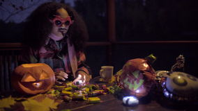 Cute black girl in devil mask frightening her friend on Halloween night. Two teen girls sharing candys after trick or treat on Halloween and jack o'lantern on stock footage