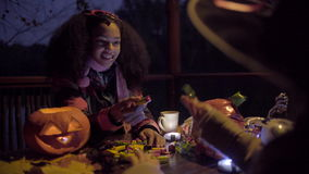 Cute black girl in devil mask frightening her friend on Halloween night. Two teen girls sharing candys after trick or treat on Halloween and jack o'lantern on stock video footage