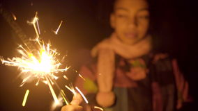 Cute black girl with dying fire of sparkler. Dying fire of sparkler in the night, black girl at the background stock footage