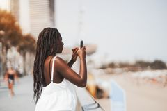 African-American female is taking pictures using her cellphone royalty free stock photos