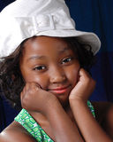 Cute black girl in white hat. Portrait of happy young black girl in fashionable white hat Royalty Free Stock Images