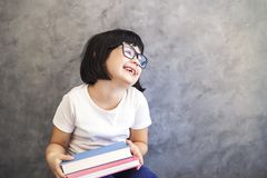 Cute black hair little girl with glasses holding books by the wa Stock Images