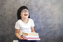Cute black hair little girl with glasses holding books by the wa Royalty Free Stock Photo