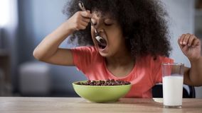 Cute black-haired curly girl eating chocolate cornflakes, unhealthy sugary food. Stock photo royalty free stock image