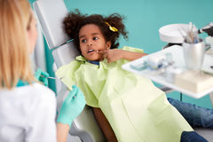 Cute black kid showing aching tooth. Very cute black kid in dental chair showing aching tooth royalty free stock images