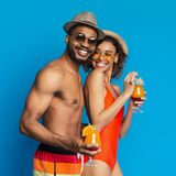 Cute black millennial couple enjoying exotic cocktails royalty free stock photography