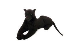 Cute black panther soft toy with long tail lies. Isolated on white Royalty Free Stock Photo