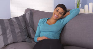 Cute black woman resting on couch smiling Stock Images