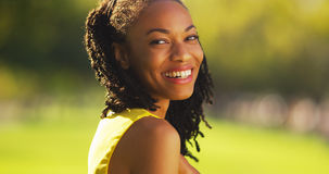 Cute black woman smiling in a park royalty free stock photography