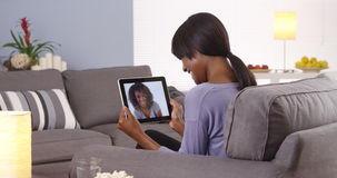 Cute black woman talking with friend on tablet Royalty Free Stock Photography