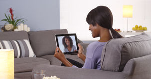 Cute black woman talking with friend on tablet Royalty Free Stock Photos