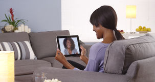 Cute black woman talking with friend on tablet Stock Image