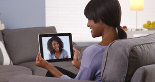 Cute black woman talking with friend on tablet Stock Photos