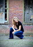 Cute Blond. Attractive blond woman crouching down in front of an old brick building. Vertically framed shot Stock Images