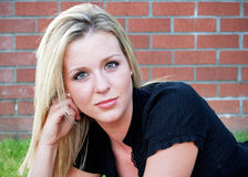 Cute Blond. Attractive blond woman crouching down in front of an old brick building. Horizontally framed close-up shot Stock Images