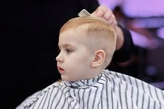 Cute blond baby boy in a barber shop having haircut by hairdresser. Hands of stylist with hairbrush. Children fashion. stock photos