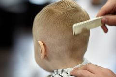Cute blond baby boy in a barber shop having haircut by hairdresser. Hands of stylist with hairbrush. stock images