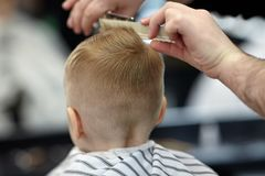 Cute blond baby boy in a barber shop having haircut by hairdresser. Hands of stylist with tools. stock image