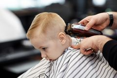 Cute blond baby boy with blue eyes in a barber shop having haircut by hairdresser. Hands of stylist with tools. Children fashion i stock image