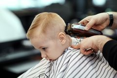 Cute blond baby boy with blue eyes in a barber shop having haircut by hairdresser. Hands of stylist with tools. royalty free stock photo