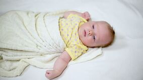 Cute blond baby falls asleep lying on a white bed.