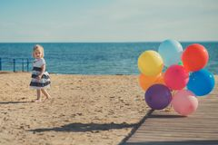 Cute blond baby girl child posing enjoying summer life time on sandy beach sea side on wooden pier with colourful plenty balloons. Wearing casual dress barefoot Stock Images
