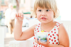 Cute blond baby girl eats ice cream and fruits Royalty Free Stock Image