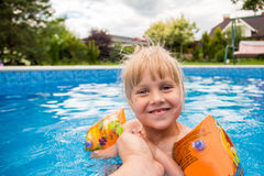 A cute blond baby girl swims at swimmig pool with blue colored water outdoors, smiles and hold parent`s hand. stock photography