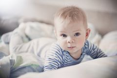 A cute blond baby lies in a light bed and looks with blue eyes at the camera. royalty free stock photo
